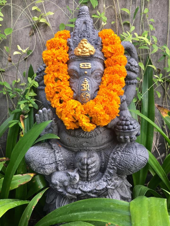 Statua religiosa con ghirlanda di fiori
